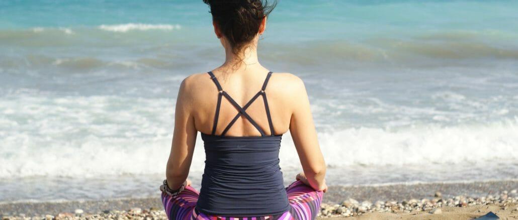 sitting on yoga mat on the beach