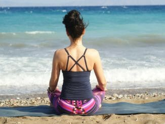 sitting on yoga mat on the beach